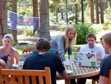 学生们 gather around a table outside of Patterson Hall to work on homework at SNU Tahoe