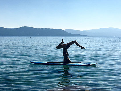 Student Kyly Clark practicing yoga on a paddleboard on Lake Tahoe