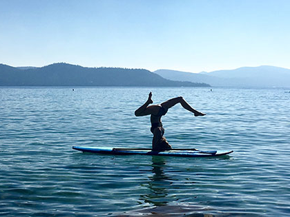 新闻学 student KyLy克拉克 does a headstand on her paddleboard on Lake Tahoe