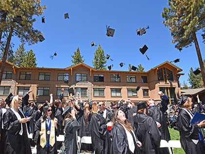 Sierra Nevada University graduates through their hats in the air at the end of the commencement ceremony.