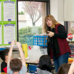 teacher in front of an enthusiastic elementary classroom