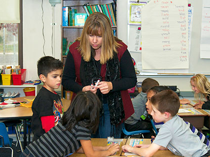 Female teacher engaged with her students in an elementary school classroom